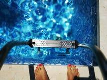 Piedi al bordo della piscina Fotografie Stock