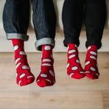 Piedi in calzini di lana Accoppi il rilassamento con una tazza della bevanda calda e scaldarsi i loro piedi in calzini di lana Immagini Stock Libere da Diritti
