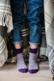 Piedi in calzini di lana La donna sta rilassandosi con una tazza della bevanda calda e sta scaldandosi i suoi piedi in calzini di immagine stock libera da diritti