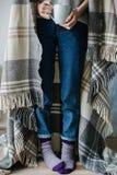 Piedi in calzini di lana La donna sta rilassandosi con una tazza della bevanda calda e sta scaldandosi i suoi piedi in calzini di fotografia stock libera da diritti