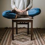 Piedi in calzini di lana La donna sta rilassandosi con una tazza della bevanda calda e sta scaldandosi i suoi piedi in calzini di Fotografie Stock