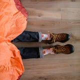 Piedi in calzini felici L'uomo sta rilassandosi vicino alla tenda e sta scaldandosi i suoi piedi in calzini felici immagini stock libere da diritti