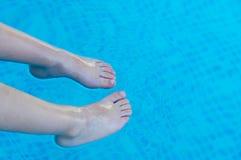 Piedi che rinfrescano nella piscina Immagini Stock