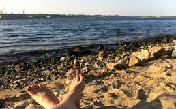 Piedi che riposano sulla riva Fotografia Stock