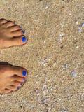 Piedi con il pedicure blu sulla spiaggia giallo sabbia, piedi della donna sulla spiaggia sabbiosa Fotografia Stock Libera da Diritti