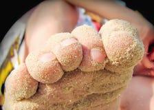 Piedi coperti di sabbia su una spiaggia Immagine Stock Libera da Diritti