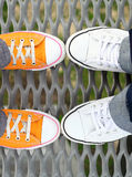 Piedi degli adolescenti del primo piano in scarpe da tennis Fotografie Stock Libere da Diritti