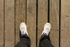 Piedi degli uomini che stanno sul ponte di legno Immagini Stock