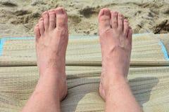 Piedi degli uomini sulla stuoia nella sabbia Fotografia Stock Libera da Diritti