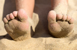 Piedi del bambino coperti di sabbia sulla spiaggia, dettaglio Immagine Stock Libera da Diritti