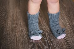 Piedi del bambino nei calzini del topo di inverno sul pavimento di legno Fotografia Stock