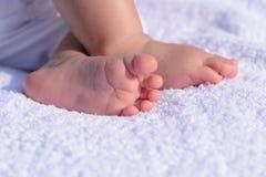 Piedi del bambino sulla coperta bianca Immagini Stock