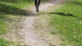 Piedi del corridore che corrono su una strada rurale