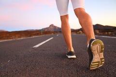 Piedi del corridore che corrono sul primo piano della strada sulla scarpa Fotografia Stock