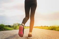 Piedi del corridore che corrono sul primo piano della strada sulla scarpa e sulla luce solare Fotografia Stock