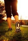 Piedi del corridore dell'atleta che corrono sull'erba immagine stock
