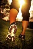 Piedi del corridore dell'atleta che corrono sull'erba immagine stock libera da diritti