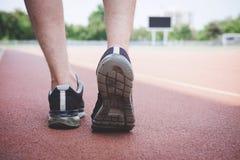 Piedi del corridore dell'atleta che corrono sulla pista della strada, concetto di benessere di allenamento di trotto di esercizio immagine stock libera da diritti