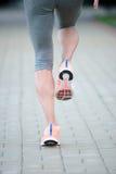 Piedi del corridore dell'atleta che funzionano sul primo piano della strada sul pattino fitne della donna Immagini Stock