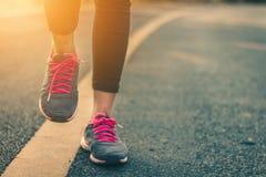 Piedi del corridore delle donne sulla strada nel benessere di allenamento Immagini Stock