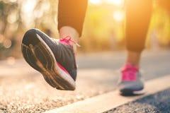 Piedi del corridore delle donne sulla strada nel benessere di allenamento Immagine Stock