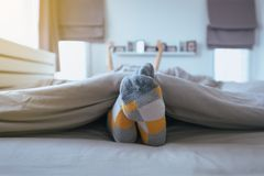 Piedi del fuoco del piede con i calzini, piedi ed allungamento pigro sul letto dopo avere svegliato Fotografie Stock