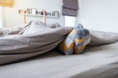 Piedi del fuoco del piede con i calzini, piedi ed allungamento pigro sul letto dopo avere svegliato Fotografia Stock Libera da Diritti
