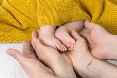 Piedi del neonato in mani del genitore fotografia stock libera da diritti