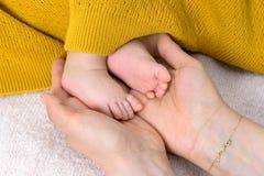Piedi del neonato in mani del genitore immagini stock