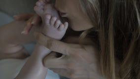 Piedi del ` s del bambino in mani del ` s della madre video d archivio