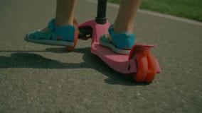Piedi del ` s del bambino in sandali che spingono mentre guidando motorino stock footage
