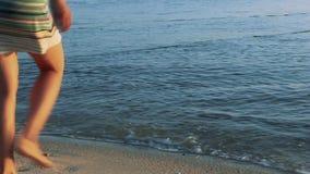 Piedi del ` s della donna in oceano sulla spiaggia stock footage