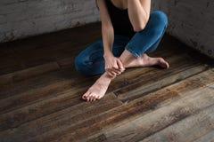Piedi del ` s della donna sul pavimento Una ragazza in jeans sta sedendosi sul pavimento Belle gambe sexy nude femminili lunghe c immagini stock