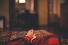 Piedi del ` s della ragazza sul letto Fotografia Stock Libera da Diritti