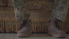 Piedi del soldato in scarpe dell'esercito, chi che si siede sul vecchio sofà, bottiglia di birra che sta vicino sul pavimento Le  stock footage
