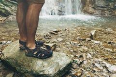Piedi del viaggiatore sulla pietra sul fondo della cascata che fa un'escursione concetto di viaggio di viaggio di viaggio immagini stock