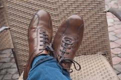 piedi dell'incrocio sulla sedia con le scarpe di cuoio fotografie stock