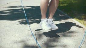 Piedi dell'uomo che saltano con una corda, allenamento d'inscatolamento all'aperto al giorno soleggiato video d archivio