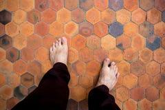Piedi dell'uomo che stanno sulle mattonelle dell'argilla Immagini Stock Libere da Diritti