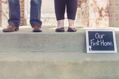 Piedi dell'uomo e della donna che comprano la loro nuova casa che tiene il nostro primo segno domestico Fotografia Stock Libera da Diritti
