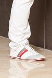 Piedi dell'uomo in pantaloni e scarpe bianchi fotografie stock