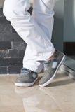 Piedi dell'uomo in pantaloni e scarpe bianchi immagini stock