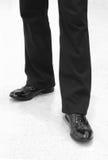 Piedi dell'uomo in pantaloni neri e pattini di cuoio Immagini Stock Libere da Diritti