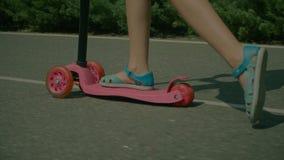 Piedi della bambina in sandali che guidano il motorino di spinta archivi video