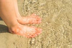 Piedi della donna in acqua sulla spiaggia Immagine Stock