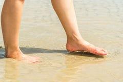 Piedi della donna in acqua sulla spiaggia Fotografie Stock Libere da Diritti
