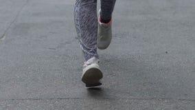Piedi della donna che corrono al rallentatore, corridore della città nei funzionamenti delle scarpe su calcestruzzo in parco video d archivio