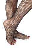 Piedi della donna con le calzamaglia del fishnet sopra bianco Fotografia Stock