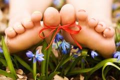 Piedi della donna a piedi nudi in fiori. Arco del nastro Immagine Stock Libera da Diritti