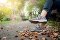 Piedi della donna in scarpa da tennis su erba verde nel parco immagine stock